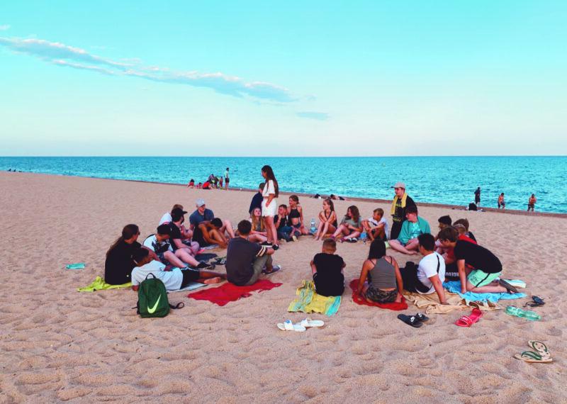 Foto der Mittleren Ferienfahrt. Eine Gruppe von Kindern und Jugendlichen am Strand.